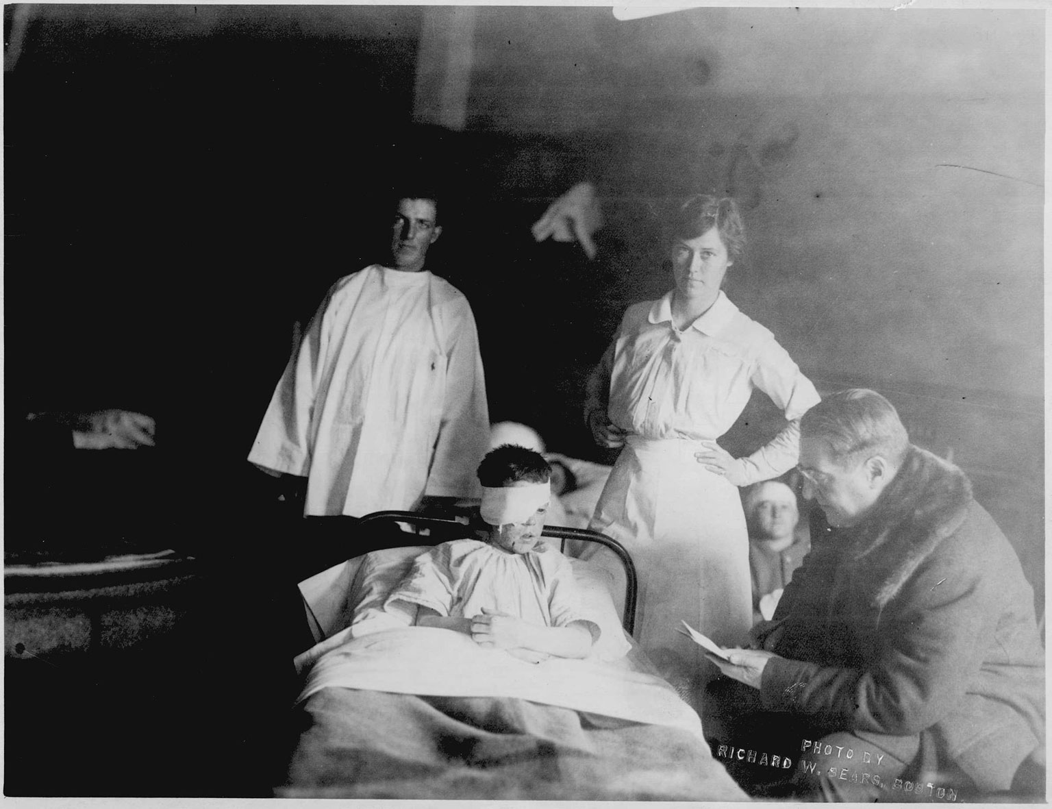 George Arthur, wounded in the explosion, sits with nurse Edith Choate, A.C. Ratshesky, and an unnamed man.