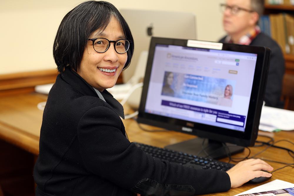 Woman at a computer using AmericanAncestors.org